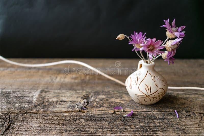 Bukett av få lila blomma Xeranthemum på den runda leravasen på wo arkivfoton