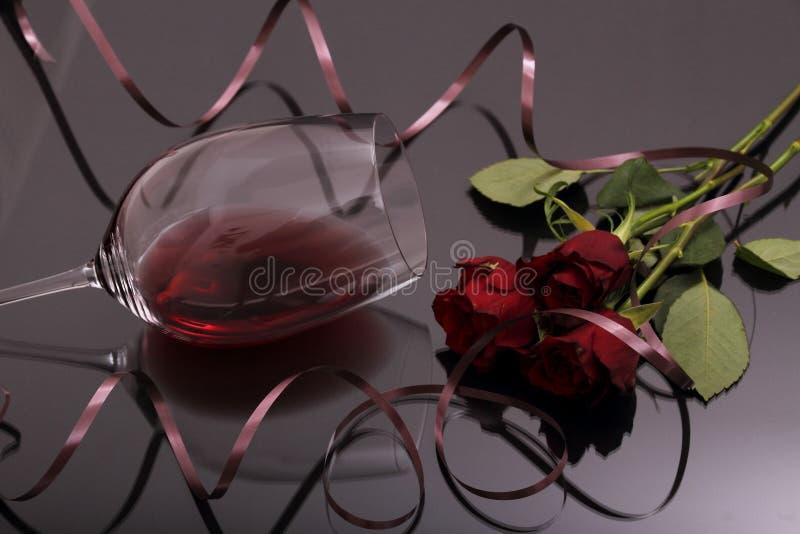 Bukett av glass rött vin för rosor och på svart royaltyfri fotografi