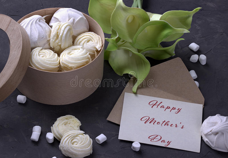 Bukett av gräsplangulingcallas med marshmallower i en trärund ask och kuvertet med att märka lycklig dag för moder` s på grått co arkivfoton
