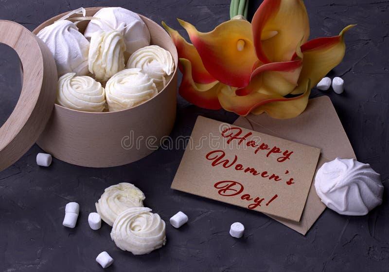 Bukett av gräsplangulingcallas med marshmallower i en trärund ask på en grå träbakgrund som märker lyckligt engelska för dag för  arkivbild