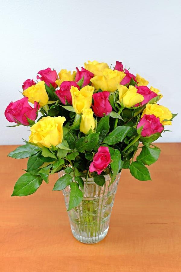 Bukett av gula och rosa rosor i en glass vas arkivfoto