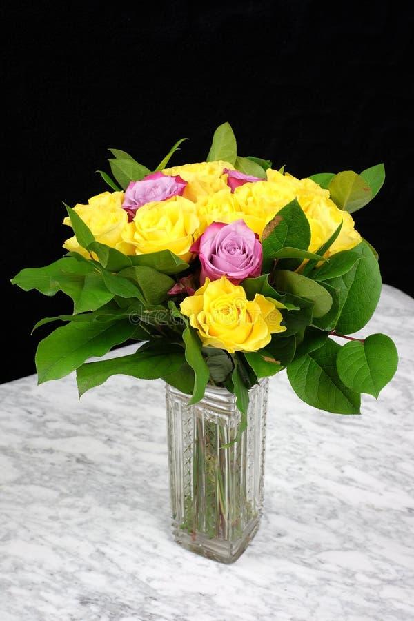 Bukett av gula rosor med tre lilor i den glass vasen royaltyfria bilder