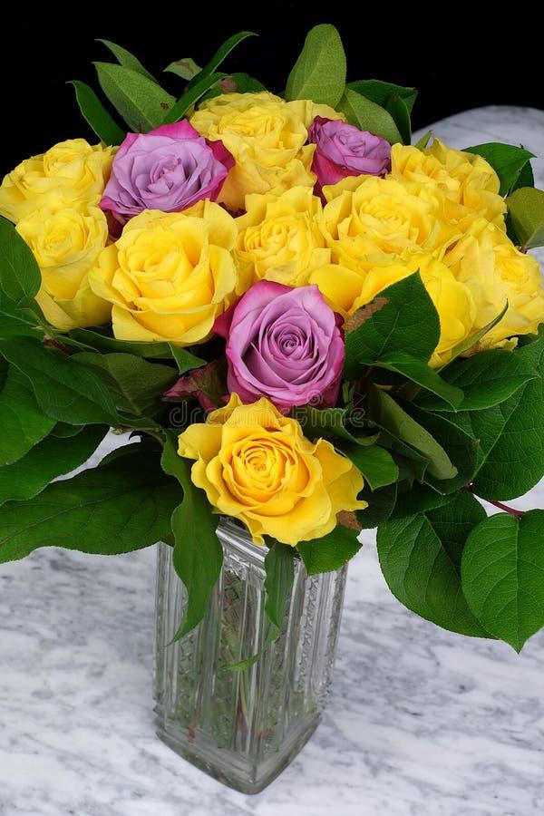 Bukett av gula rosor med tre lilor i den glass vasen arkivbilder