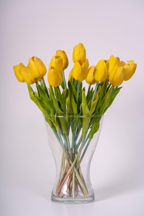 bukett av gula tulpan som står i en vas royaltyfria bilder