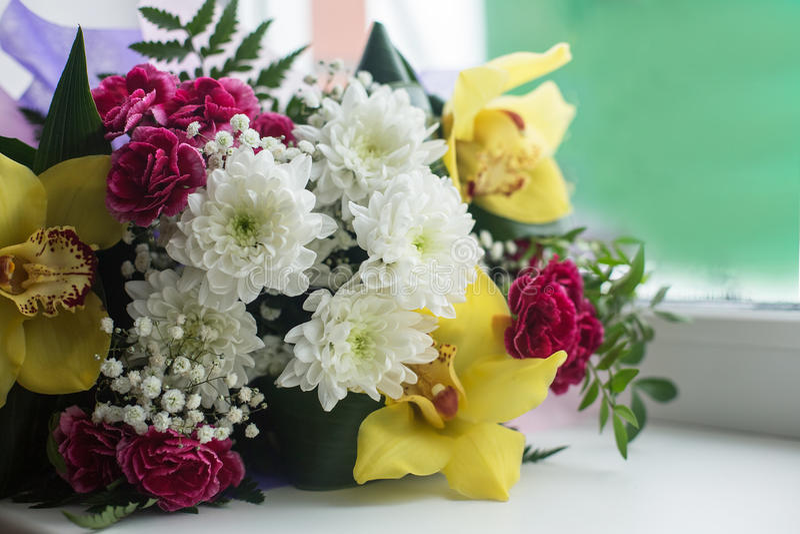 Bukett av härliga blommor i fönstret royaltyfri bild