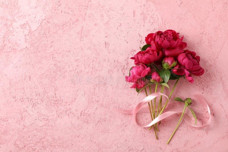 Bukett av härliga pioner och det rosa bandet på färgbakgrund arkivfoton