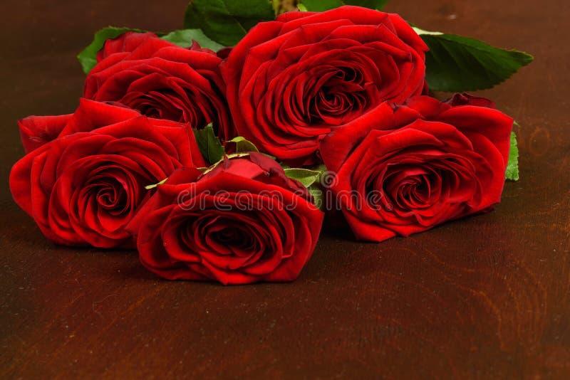 Bukett av härliga röda rosor på en mörk träbakgrund fotografering för bildbyråer