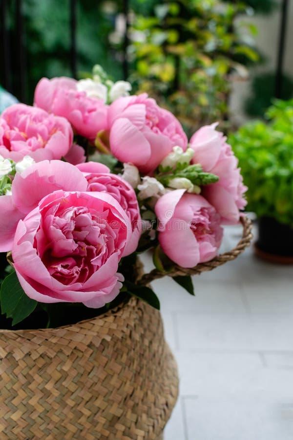 Bukett av härliga rosa pioner i sugrörkorg royaltyfri foto