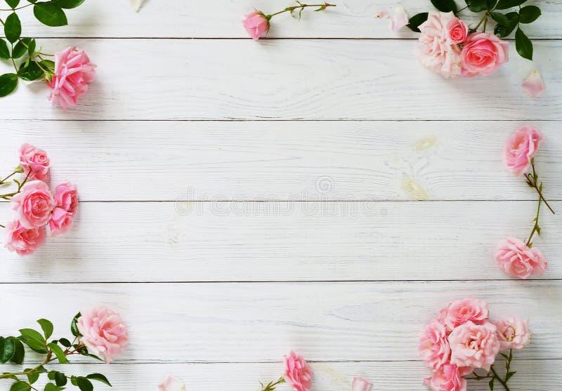 Bukett av härliga rosa rosor och gåvan i rosa emballage på vit träbakgrund Top beskådar kopiera avstånd royaltyfria foton