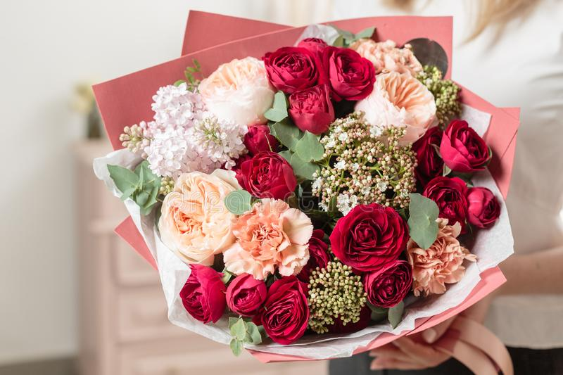 Bukett av högt rött färgat härlig lyxig grupp av blandade blommor i kvinnas hand arbetet av blomsterhandlaren på a royaltyfri bild