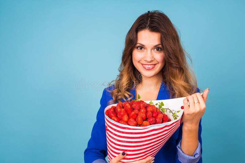 Bukett av jordgubbar i händerna av en flicka på blå bakgrund arkivbild