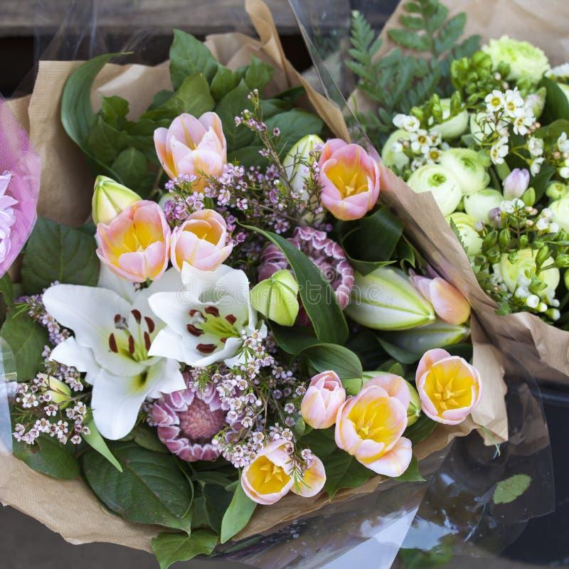 Bukett av knoppar av liljor, rosa tulpan och proteaen royaltyfria bilder