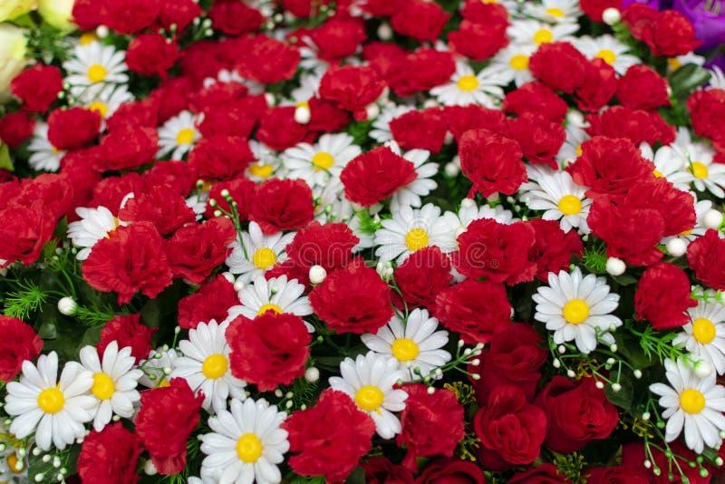 Bukett av konstgjorda blommor av den vita kamomillen och röda nejlikor, arkivfoton