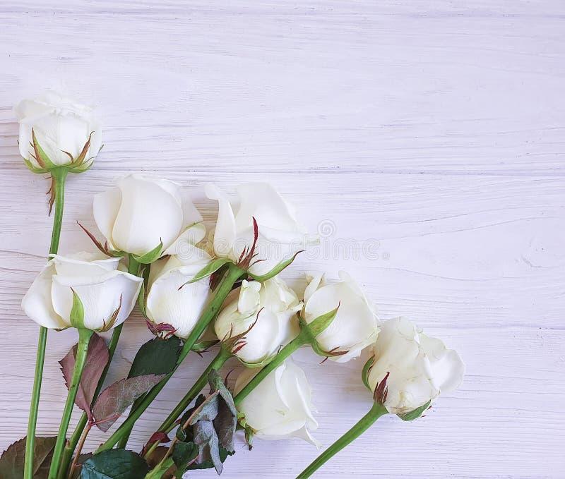 Bukett av lantligt för tappning för vita rosor härligt på en vit träbakgrund royaltyfria foton