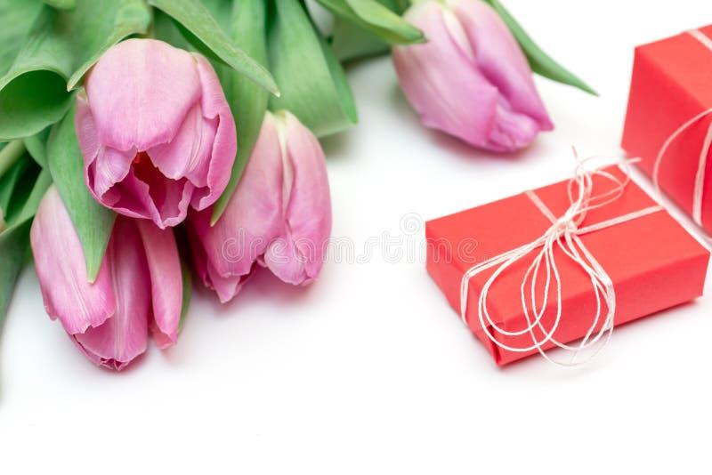 Bukett av lila vårtulpan och röda gåvaaskar på den vita tabellen, kvinnan eller mors dagbegreppet arkivfoto