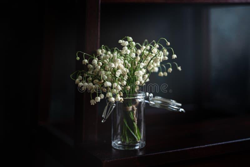 Bukett av liljekonvaljer i liten krus med str?len av ljus, m?rk bakgrund royaltyfri bild