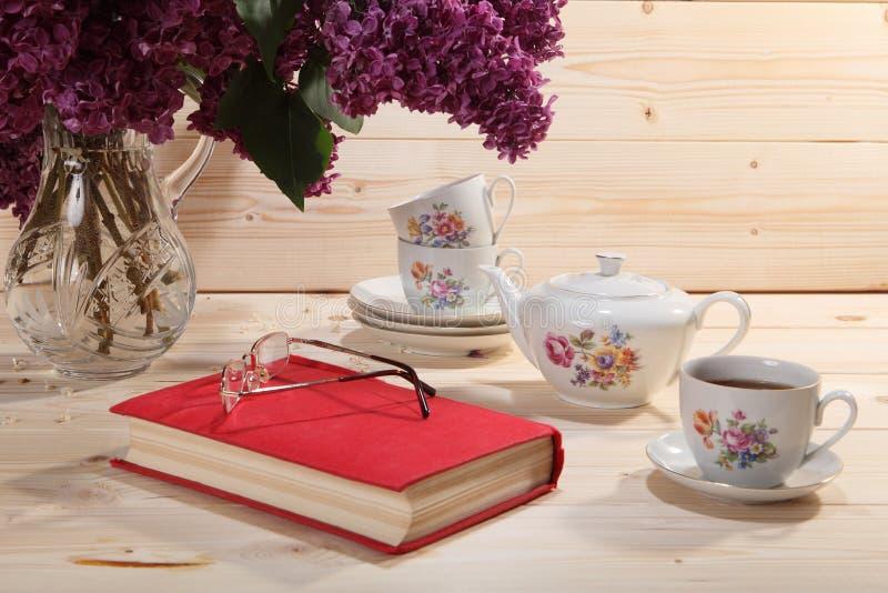 Bukett av lilor, boken, anblickar, tekannan och kopp te royaltyfria bilder