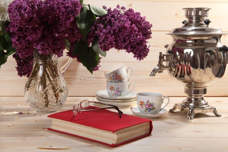 Bukett av lilor, samovar, kopp te, boken och anblickar royaltyfri foto