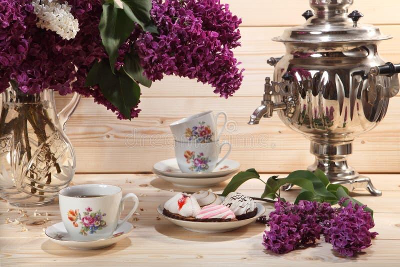 Bukett av lilor, samovar, kopp te och kexet på träbac royaltyfri bild