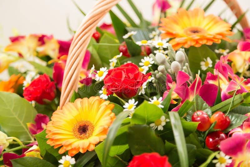 Bukett av mång--färgade blommor i en wattled korg arkivfoton