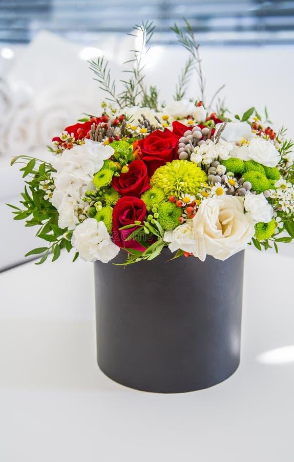 Bukett av mångfärgade blommarosor i lyxig gåvaask fotografering för bildbyråer