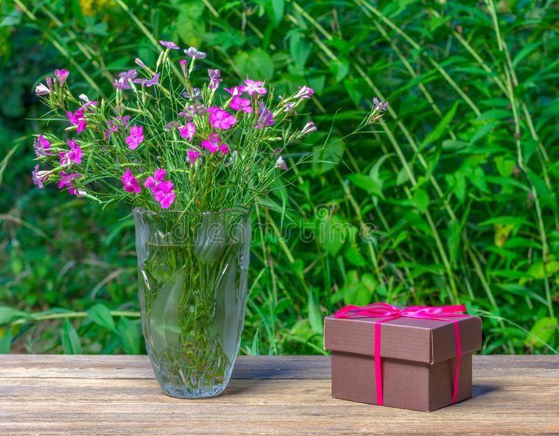 Bukett av nejlikor i en glass vas och en brun ask med en gåva royaltyfri bild
