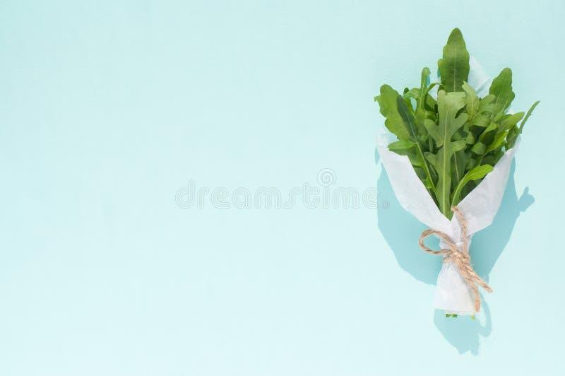 Bukett av nya gröna arugulasidor i vitt hantverkpapper som isoleras på ett ljus - blå bakgrund arkivbild