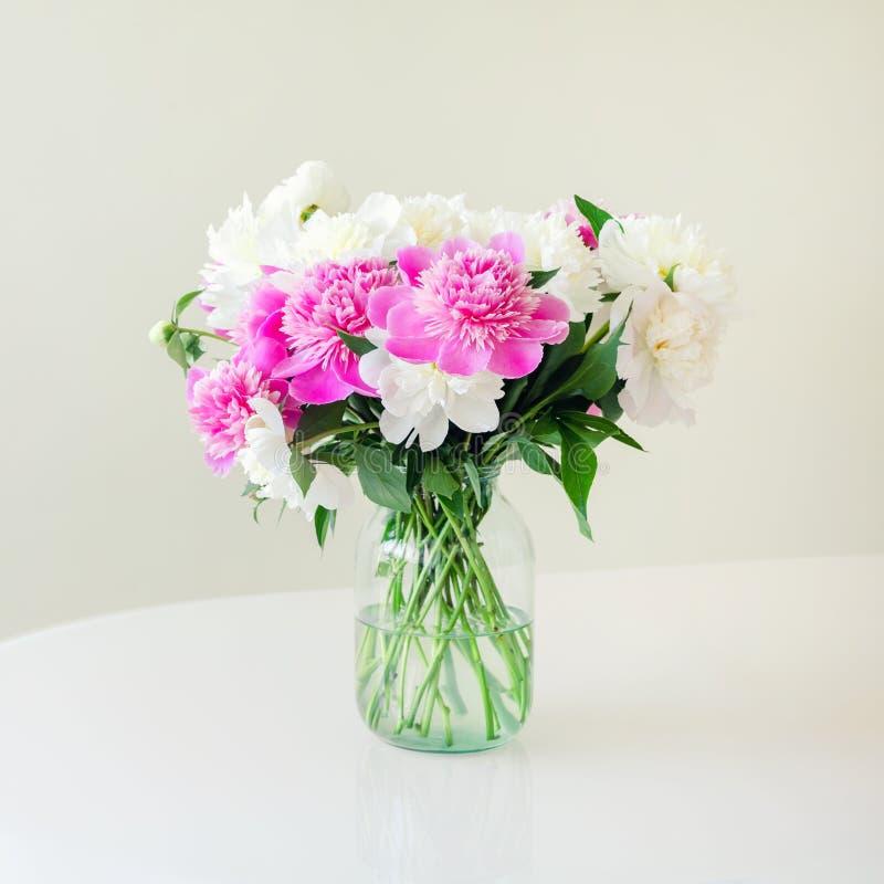 Bukett av nya stora rosa, vita och kräm- pioner i enkel exponeringsglaskrus på ögonkasttabellen inomhus Vas med härligt royaltyfria bilder