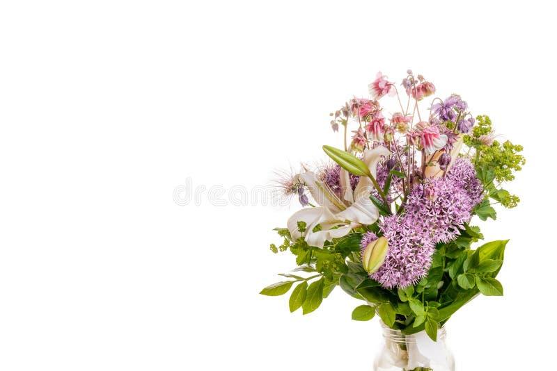Bukett av nya vårblommor, vit lilja, dekorativa lökbollar, aquilegia, manschett, dams ansvar i en exponeringsglaskrus royaltyfria foton