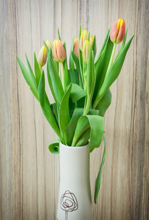 Bukett av orange tulpan i vasen på träbakgrunden fotografering för bildbyråer