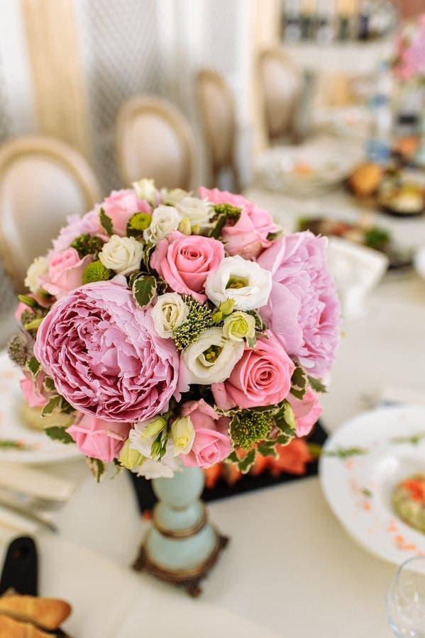 Bukett av pioner och rosor i en vas på en tjänad som tabell arkivfoto