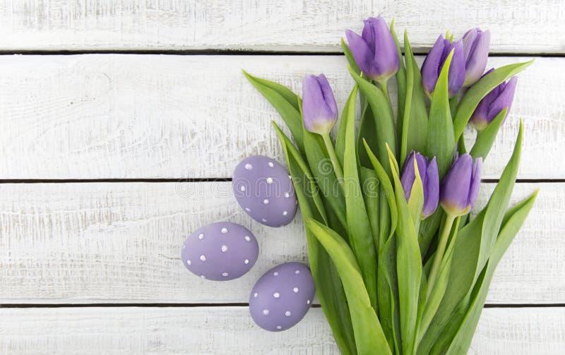Bukett av purpleviolettulpan och målade easter ägg på whit arkivfoto