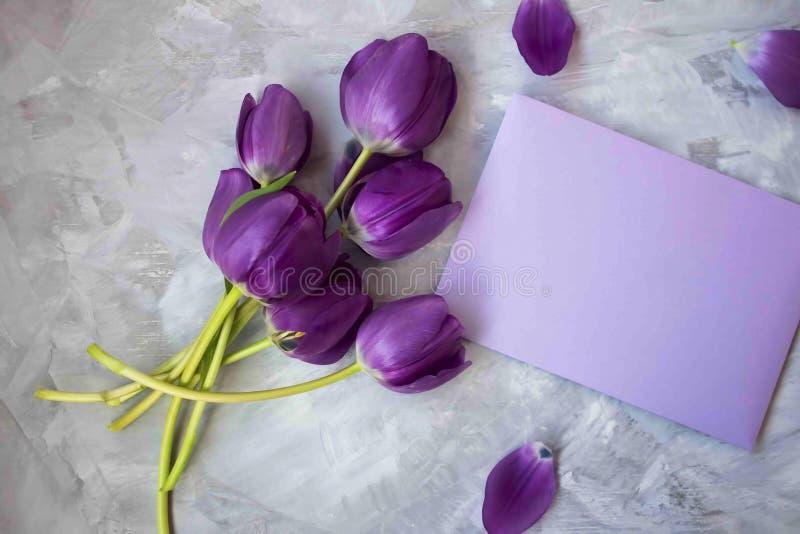 Bukett av purpurfärgade tulpan längs en förälskelsebokstav royaltyfri fotografi