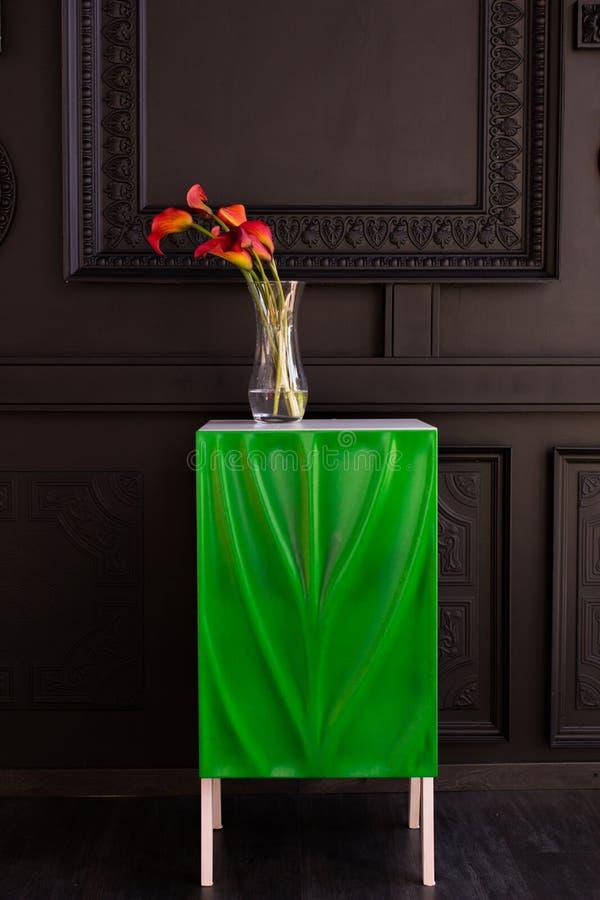 Bukett av röda callaliljor i en glass vas med en granatäpple och en eukalyptus royaltyfri fotografi