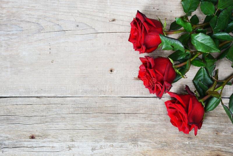 Bukett av röda rosor på träbakgrund royaltyfri bild