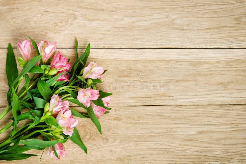 Bukett av rosa alstroemeria på träplattan royaltyfri foto