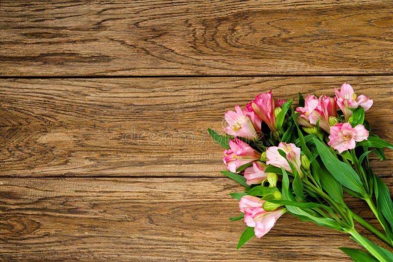 Bukett av rosa alstroemeria på träplattan fotografering för bildbyråer