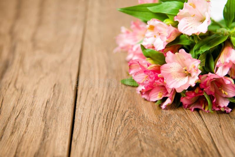 Bukett av rosa alstroemeria på träplattan royaltyfria foton