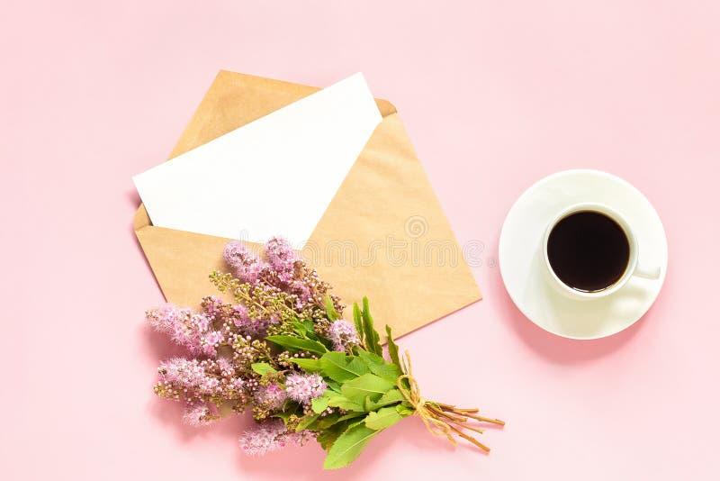 Bukett av rosa blommor, kuvert med det vita tomma kortet för text och kopp kaffe på rosa åtlöje för hälsa kort för bakgrund plan  fotografering för bildbyråer
