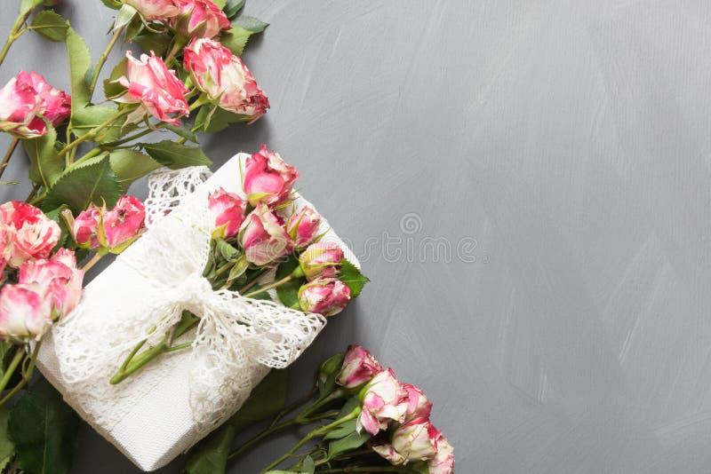 Bukett av rosa buskerosor och den kvinnliga gåvan på tappninggrå färgbakgrund Top beskådar kopiera avstånd arkivfoto