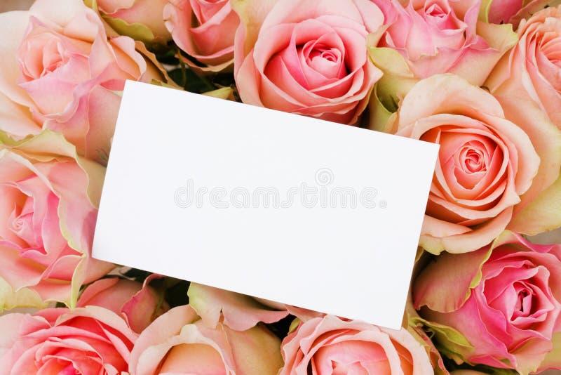 Bukett av rosa ro i basketwithhälsningskort royaltyfri fotografi