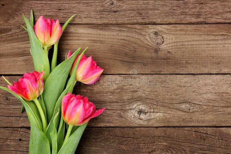 Bukett av rosa tulpanblommor mot en lantlig träbakgrund arkivbilder