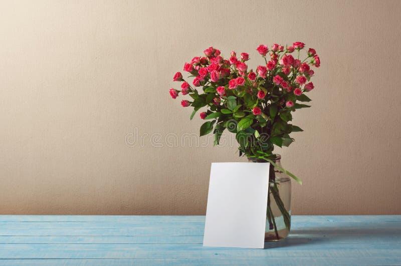 Bukett av rosor med ett tomt hälsningkort royaltyfri foto