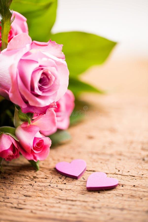 Bukett av rosor med två lilla hjärtor på en träbakgrund arkivfoto