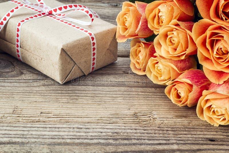 Bukett av rosor och gåvaasken på en gammal trätabell kopiera avstånd royaltyfria bilder