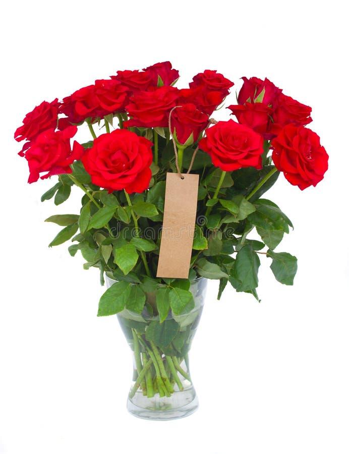 Bukett av scharlakansröda rosor i vas med etiketten arkivbilder