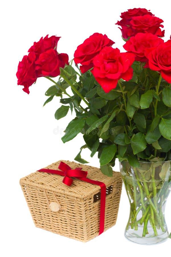 Bukett av scharlakansröda rosor i vas med gåvakorgen arkivfoton