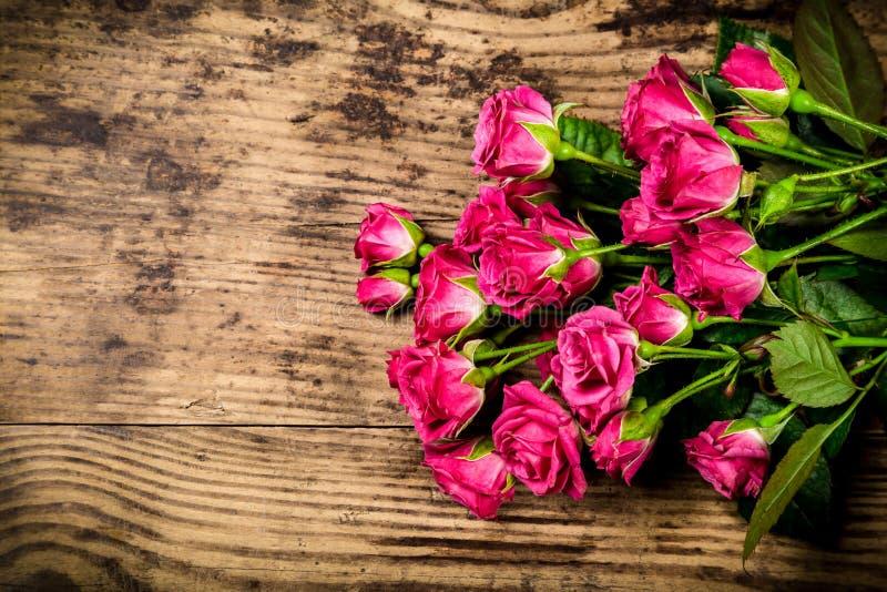 Bukett av små rosa rosor på träbakgrund royaltyfri fotografi