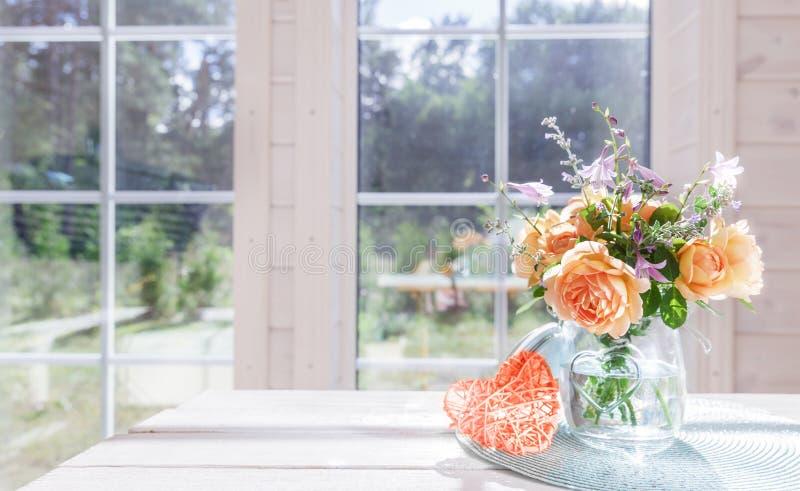 Bukett av sommarrosor i den glass vasen nära fönstret royaltyfri fotografi