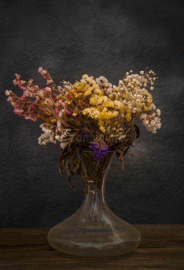 Bukett av torkade blommor som glömms i vinden arkivbild